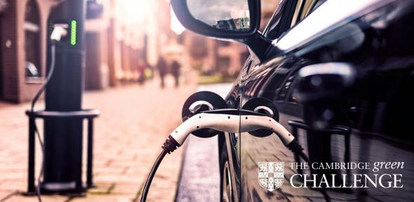 An electric car plugged into a charging point with the University of Cambridge Green Challenge Logo